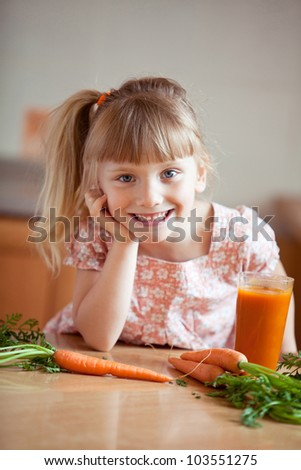 Nice blond baby girl with glass of carrot juice