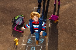 Nice blond boy jumping over hopscotch game after school with bags and scooter laying near