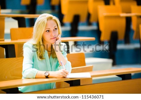 Nice blonde blue-eyed bored student girl in auditorium listening and propping up her head with a hand