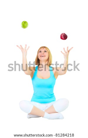 Nice blonde sits in a pose of a lotus and juggles red and green apples, isolated over white
