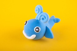 Nice blue toy whale made of modelling dough laying on yellow background