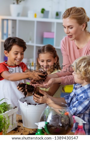 Nice botany lesson. Boys and girl attending botany lesson feeling cheerful with teacher while potting plants Photo stock ©