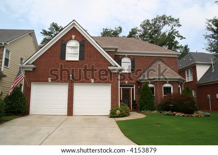Nice brick home and lawn with American Flag out front