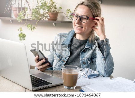 Nice business woman in a cozy workplace works with pleasure
