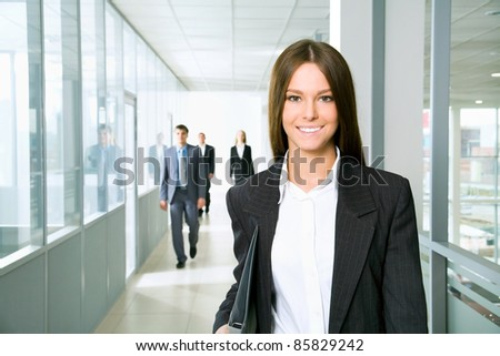 Nice business woman walking down the corridor office