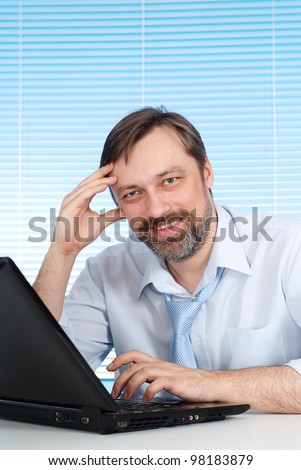 Nice businessman sitting at a table and working on a light background - stock photo
