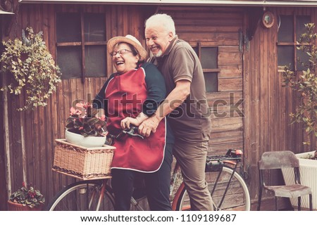 Nice caucasian people enjoy leisure outdoor both on a single bike lauhing like crazy. together funny moments at home outside. vintage filter and colors for joyful and laugh concept #1109189687