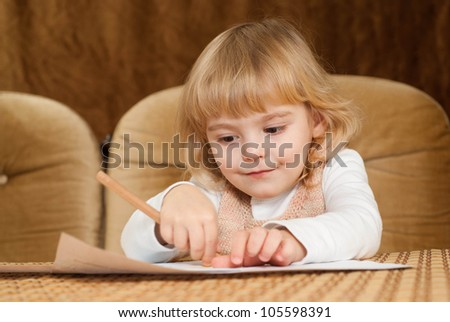 Nice Caucasian young baby draws a table on a brown background