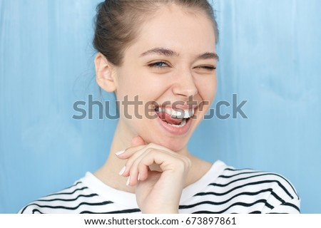Nice close-up portrait of young european girl. Happy tricky cute female with smiling face blinking at camera in a playful manner, standing against blue background. Winking expression concept