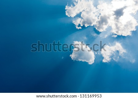 Nice clouds with sun rays in blue sky