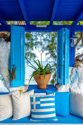 Nice composition of blue and white colors, window with sea view and greek flag, Crete, Greece