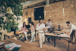 Nice confident experienced people director calling employee discussing document analysis at modern industrial loft brick open space style interior workplace workstation