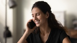 Nice conversation. Happy young latin female engaged in pleasant phone talk holding modern cell device at ear. Smiling female student speaking on phone sharing good news positive emotions with friend