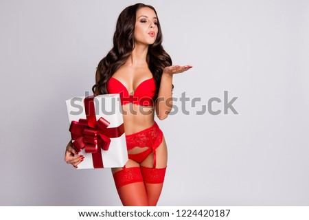 Nice cool winsome delicate adorable attractive charming slim curly-haired girl wearing lingerie, holding big gift box with bow, kiss you, isolated over white background