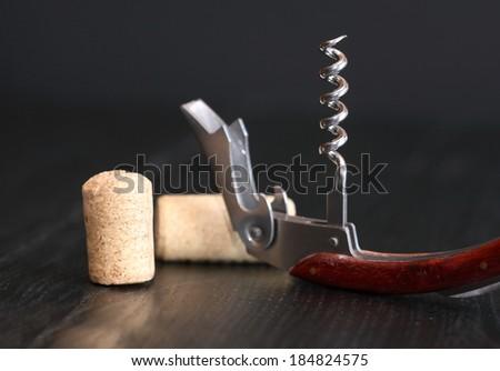 Nice corkscrew with wooden handle near cork on dark background - stock photo