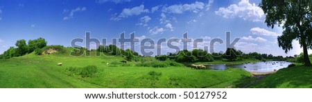 Nice country panorama with river, sheep and green field