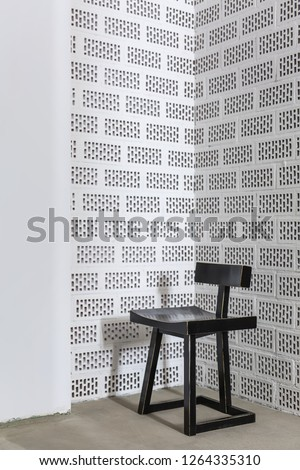 Nice dark wooden chair on the concrete floor on the background of the white brick wall. Closeup. Vertical.