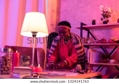 Nice day. African american plump fortune-teller wearing huge earrings looking pleased while shifting cards