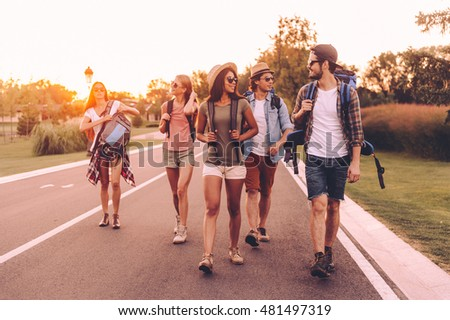 Nice day for hiking. Group of young people with backpacks walking together by the road and looking happy  #481497319