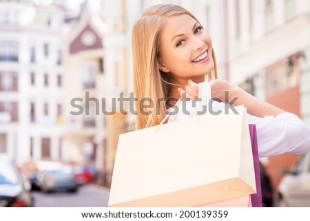 Nice day for shopping. Rear view of beautiful young cheerful woman holding shopping bags and looking over shoulder while standing outdoors