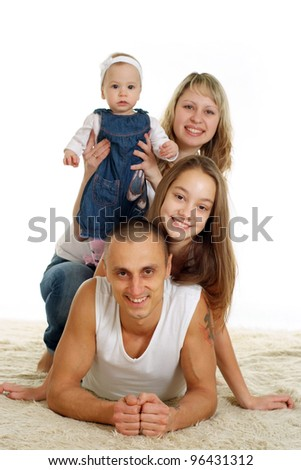 Nice family of four people lying on background - stock photo