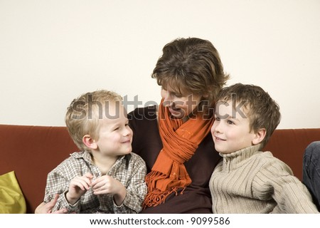 Nice family picture of a mother sitting with her two sons on a couch.