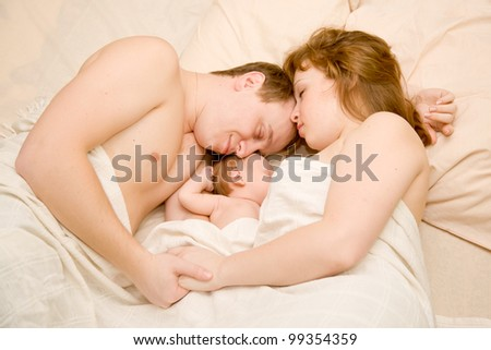 Nice family sleeping together in a white bed. Mother, father and newborn baby. Baby eating the mother's breast. Happy dream. Woman and man holding hands