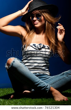 nice fashionable long haired woman is sitting on grass