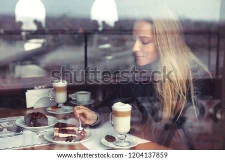 Nice female in cafe eating cake and drinking latte in warm cozy atmosphere, enjoying sweet tasty dessert, casual urban life of young people