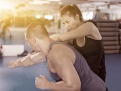 Nice female is fighting with trainer on the self-defense course for woman in sport club