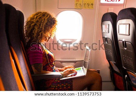 nice female with curly hair sitting inside the airplane ready to flight for the nex destination use a laptop during the trip. work or pleasure activity for beautiful middle age woman traveler.  #1139573753