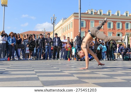 NICE, FRANCE â?? APRIL 11, 2015: A group of street dancers performing a break dance routine on Place Massena in Nice, France.