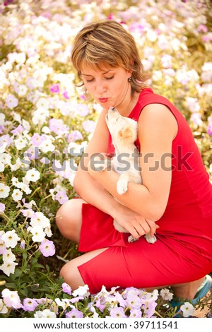 Nice girl holds in hands of small puppy and kisses it, against the big flower bed.