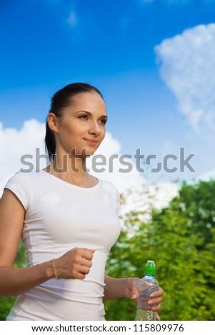 nice girl in white t-shirt jogging in summer morning
