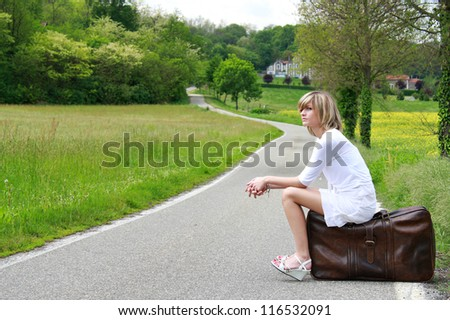 Nice girl is waiting on a suitcase at the border of a country road. Travel conceptual