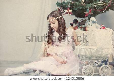 Nice girl plays with doll around Christmas tree