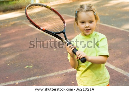 Nice girl with racket in hands playing game of tennis
