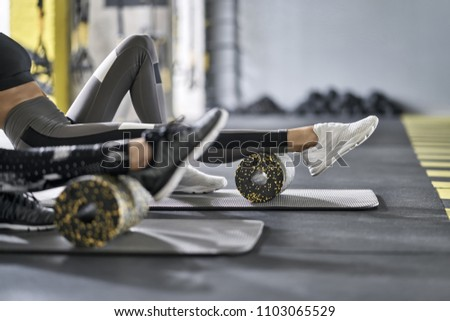 Nice girls are training with black-yellow foam rollers on the gray mats in the gym. They are wearing the multicolored sportswear: pants, tops and sneakers. Closeup. Horizontal. #1103065529