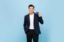 Nice handsome southeast Asian man in semi formal blazer holding credit card in light blue isolated studio background
