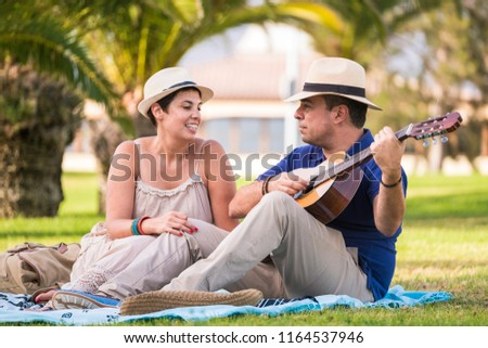 nice happy alternative couple enjoy the outdoor leisure activity together with love and fun playing an acoustic guitar and singing some songs. sitting on the grass and relaxing, middle age people