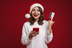 Nice happy girl in Santa Claus hat posing with credit card and mobile phone isolated over red background