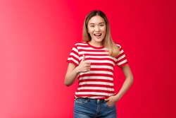 Nice idea my approval. Pleased satisfied good-looking blond asian girl show thumb up and smile, give positive reply, agree wish good luck, judge excellent work, stand red background
