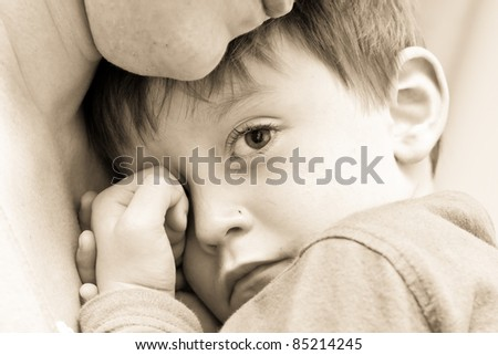Nice image of a young upset boy cuddling his mum