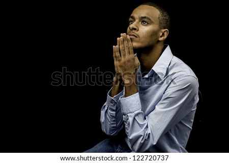 Nice isolation of a young african american black male praying with plenty of space for custom text