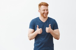 Nice job man, like it. Pleased good-looking happy male friend with ginger hair and brislte, showing thumbs up and smiling broadly, giving positive feedback, sharing his positive opinion over grey wall