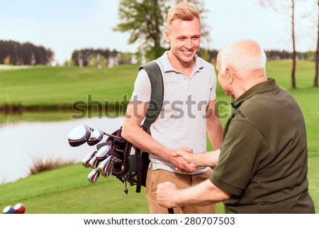 Nice job. Young and old golf players standing on golf course with golf equipment and shaking hands.