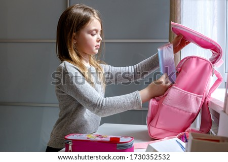 Nice kid preparing for school her backpack. First day of school. Back to school. Little schoolgirl collecting books in a school bag. Young schoolgirl going to get knowledge.
