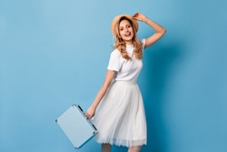 Nice lady in light skirt and white T-shirt posing on blue background. Girl in boater holds suitcase