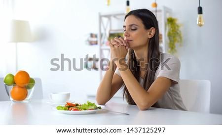 Nice lady praying, blessing God for dinner, eating healthy vegetarian salad
