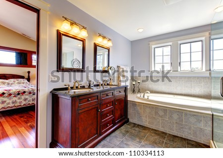 Nice lavender bathroom with tub and wood cabinet with two sinks and tile floor.